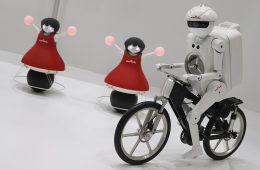 Las Cheerleaders (I) y el robot Seisaku-kun (D), de la compañía nipona de tecnología Murata, muestran sus destrezas durante la feria tecnológica CEATEC en Makuhari, cerca de Tokio, Japón.